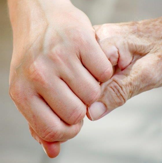 Image of Young person and elderly person holding hands