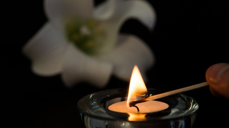 Image of Hand lighting tea light candle with white lily in background