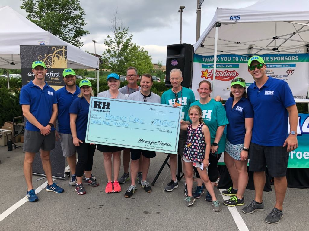 heroes for hospice runners pose with large check