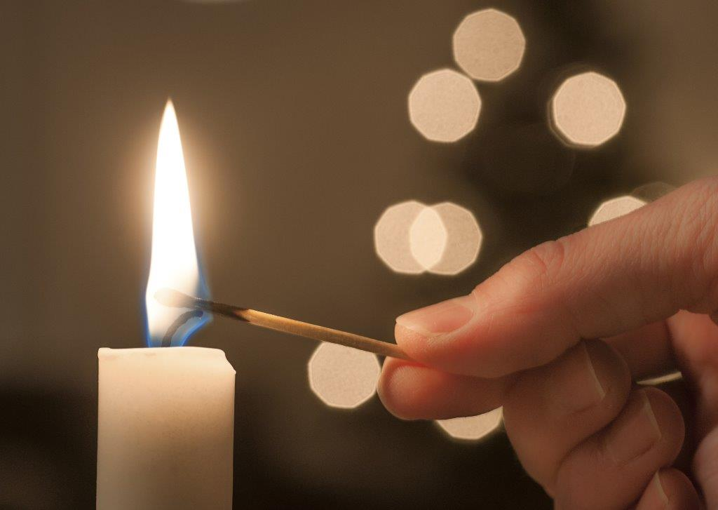 Image of Candle Being Lit in front of holiday lights
