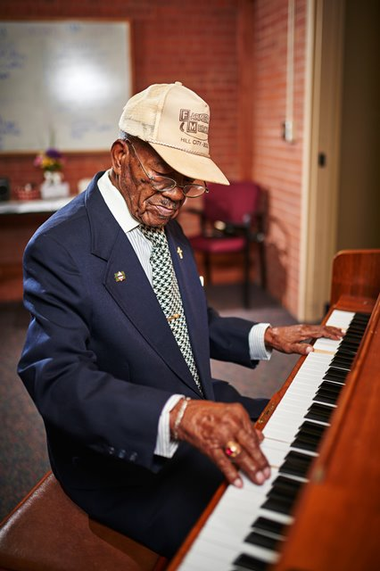 Photo of Midland Care PACE Participant Chester playing the piano at the Topeka PACE Center